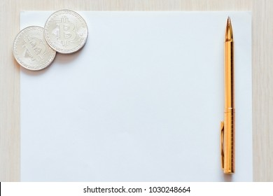 Close up view of table and paper, two coins symbol of bitcoin, golden pen on it. Mockup for design.