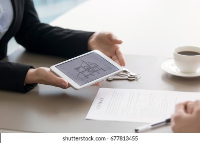 Close up view of tablet in female hands with architectural plan of two story house section cut drawing draft and contract on the table. Home loan, taking mortgage to buy own cottage or villa