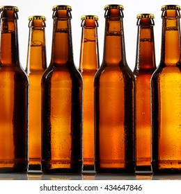 Close up view of tall beer bottles with metal caps and condensation covering each one