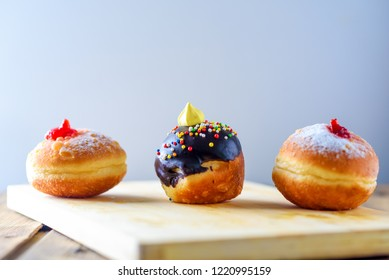 Close up view of tasty various donuts on wood background. Hanukkah celebration concept. Round jelly or jam doughnut sufganiyot and chocolate sufganiyah for Chanukah Jewish holiday on wooden background