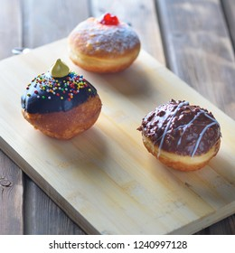 Close up view of tasty various donuts on wood background. Hanukkah celebration concept. Round jelly or jam doughnut sufganiyot and chocolate sufganiyah for Chanukah Jewish holiday.