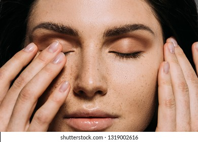 close up view of tender girl with freckles on face touching closed eyes