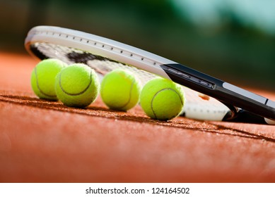 Close up view of tennis racket and balls on the clay tennis court