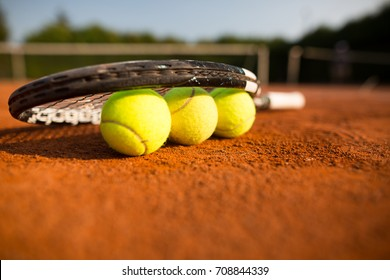Close up view of tennis racket and balls on the clay tennis court, recreational sport