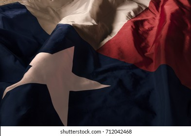close up view of the Texas Lone Star flag isolating the three separate colors and the single star amongst shadow, high lights and waves