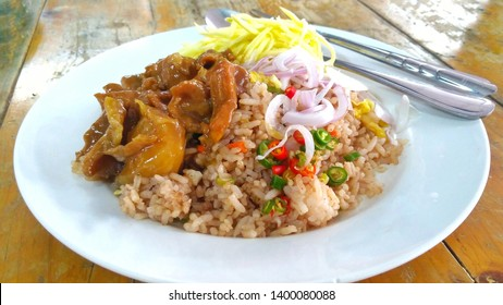 Close up view of Thai Rice Mixed with Shrimp paste or Kao Kluk Gapi on wooden table with spoon and fork