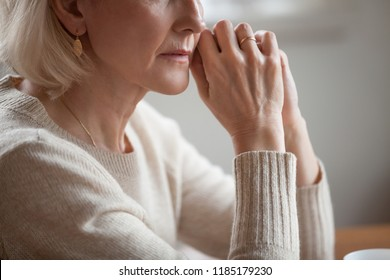 Close up view of thoughtful mature woman worried concerned about problems or disease, middle aged grey haired senior lady getting older thinking of loneliness depression grief anxiety concept