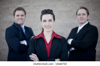 close view of three businesspeople standing with arms crossed in formal wear all smiling and looking at camera
