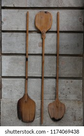 Close up view of three wooden pizza peels hanging at a grey painted wall for decoration. Tapered edge design to better slide under the pizza. Vintage image of large ancient spoons. Abstract picture.