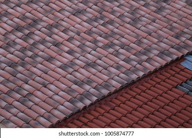 Close up view of a tiled roof of a house. Two kinds of tiles, orange and pink with oblique lines. Textured surface with waves forms. Top of a classic house in south of France. Abstract image.