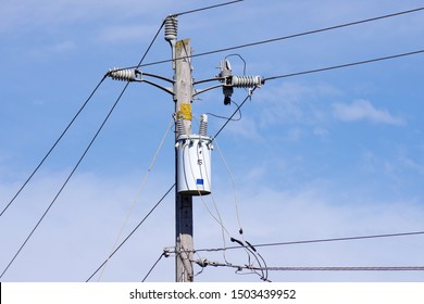 Close view of the top of a electricity distribution pole with power lines and isolators and a transformer seen against a blue sky with some white clouds