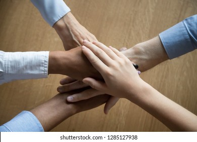 Close up view from top women and men diverse businesspeople putting hands together above the table express unity and support. Symbol gesture of friendship togetherness and like-minded people concept
