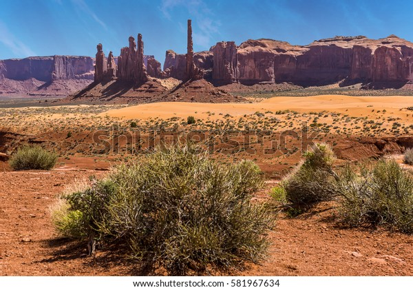 Close up view of Totem Pole Spire and Yei Bi Chei Spires with mesa backdrop in Monument Valley tribal park in springtime