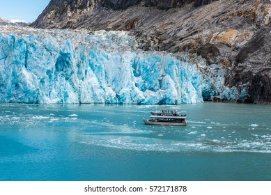 Close up view of tourist boat next to glacier face with icy ocean waters