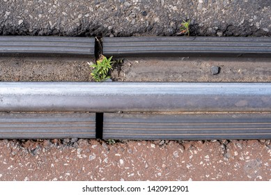 close view of train tracks and rubber seals with tarmac