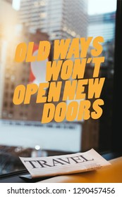 """close up view of travel newspaper with """"old ways wont open new doors"""" quote on window and new york city on background"""