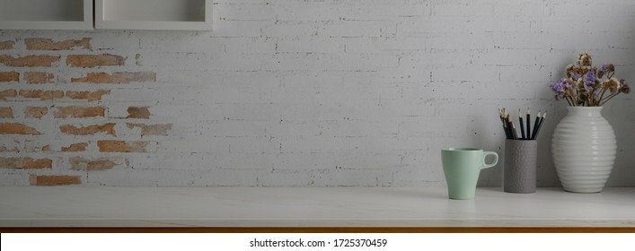 Close up view of trendy worktable with stationery, coffee mug and copy space on marble desk with white brick wall