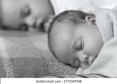 close up view of two children, newborn baby,three year old girl sleeping together on beige bed. Sisters are sleeping on couch at home.