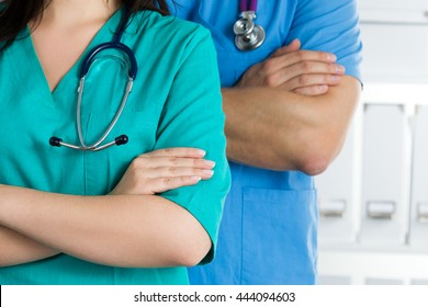 Close up view of two doctors standing with their arms crossed on chest ready to work. Health care, medical and teamwork concept.