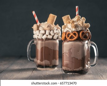 Close up view of two freakshake in mason jar on brown table. Freaked milkshake or overshake with chocolate, pretzel, marshmallow, popcorn and waffles. Trendy food concept - freak shake