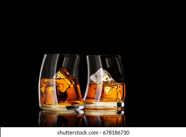 close up view of two glasses of  whiskey on black back