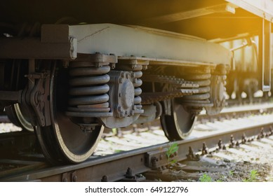 Close view of two train wheels with heavy springs on rails in sunlight warm toned vintage effect with bokeh