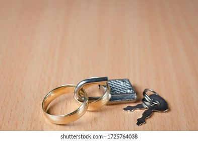 Close up view of  two wedding rings closed with a padlock representing a concept of united marriage without secrets and trust . Or  divorce between two people or infidelity