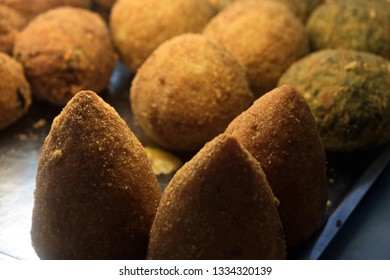 """close view of a typical sicilian snack: a ball of rice fried named """"arancino"""""""