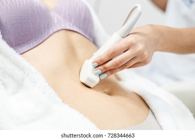 Close up view of ultrasound examination. Doctor keep holding in her hand an ultrasound transducer. Closeup of USG machine