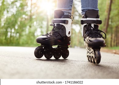 Close up view of unknown person rollerblading in park on sunny day, being on road, spending time in fresh air, enjoying hobby during vacation, fun free time activity. People and lifestyle concept.