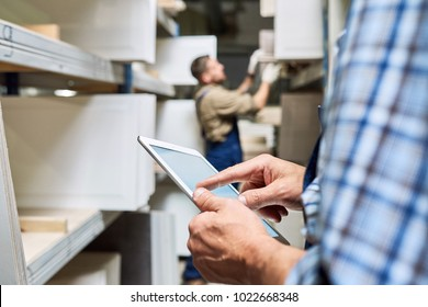 Close up view of unrecognizable worker holding digital tablet while doing inventory in factory storage room, copy space
