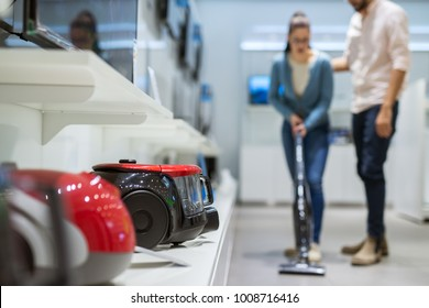 Close up view of vacuum cleaners while young stylish couple testing another behind in a tech store.