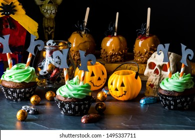Close up view of a variety of Halloween treats and decorations including caramel apples and chocolate cupcakes with witch decorations. Halloween party concept.