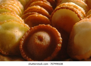 Close up view of various flavored of 'kue cucur gula merah' or 'pinjaram' or 'khanom fak bua', traditional cake made of flour and brown sugar with cinnamon or fragrant screwpine as flavouring.