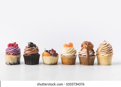 close up view of various sweet cupcakes on cake stand isolated on white
