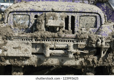 close of view of a very muddy jeep grill after off road driving through the dirt and mud.