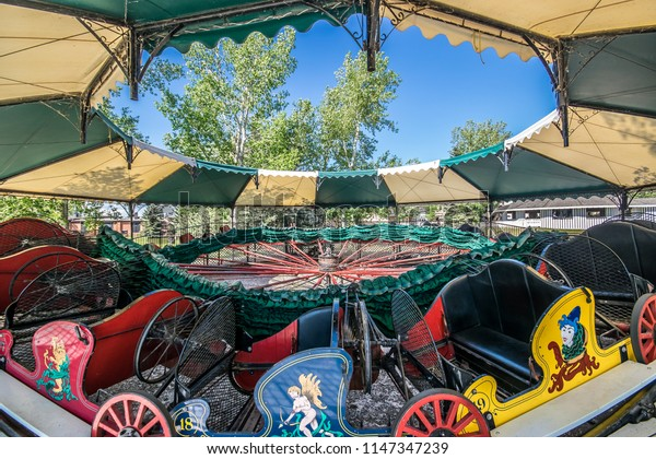 Close up view of vintage merry go round cars with bright vibrant colours.