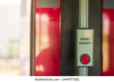 """Close up view of Vintage Red Pushbutton with """" Halte- Wunsch """", German words mean stop request button, on the white background , located beside door inner of tram which operate in Düsseldorf, Germany"""