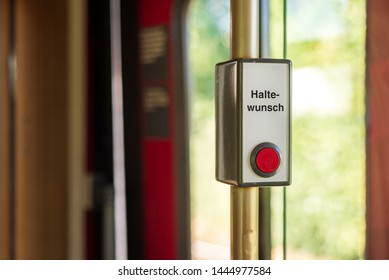 "Close up view of Vintage Red Pushbutton with "" Halte- Wunsch "", German words mean stop request button, on the white background , located beside door inner of tram which operate in Düsseldorf, Germany"