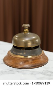 close up view of vintage rusty hotel service gold bell on white marble table with brown curtain background
