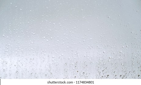 Close up view of water drops falling on glass. Rain running down on window. Rainy season, autumn. Raindrops trickle down, grey sky.