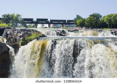 Close up view of waterfall and train passing bridge in Sioux Falls, South Dakota.