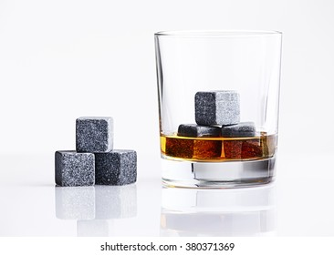 Close up view of whisky stones in the glass with whisky isolated on white background. Gray whiskey stones in the glass. Whiskey glass filled with cooling granite stones. Bourbon with ice Whisky Stones