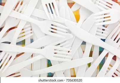 Close view of white plastic forks and knives on a colorful tablecloth.