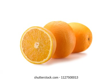 close up view of wholesome oranges with cut piece isolated on white