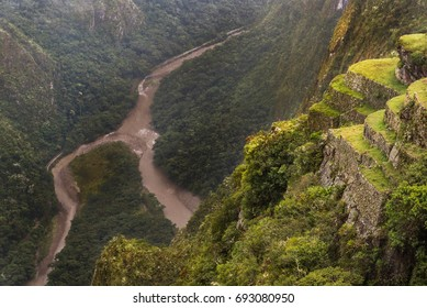 Close up view of the winding Urubamba river from the cliff of Machu Picchu through the mist and rain