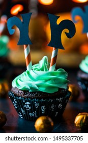 Close up view of a witch theme decorated cupcake against a blurred background of Halloween treats and decorations.