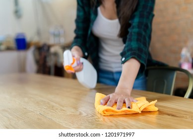 Close up view of woman cleaning a house. She is wiping dust using a spray and a orange fabric while cleaning on the table. House cleaning concept.