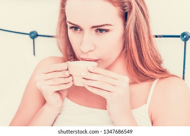Close view of woman drinking coffee in bed, in morning time.