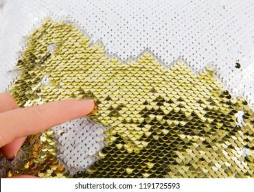 Close up view of woman finger play with gold and white shimmer sequin reversible fabric. Arts and crafts material idea concept and great stress reliever on busy holiday season.